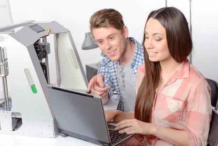Photo pour Jeune belle étudiante souriante et tapant sur un ordinateur portable tandis que son collègue l'aide avec un projet assis à côté d'elle, imprimante 3D debout près, mise au point sélective - image libre de droit