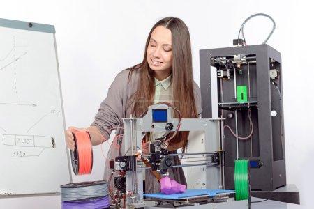 Photo pour Belle jeune étudiante brune aux cheveux longs tenant des pièces en plastique colorées d'une imprimante 3D imprimant un nouveau modèle violet dans un laboratoire - image libre de droit