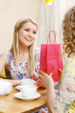 Pretty blond woman getting gift in cafe