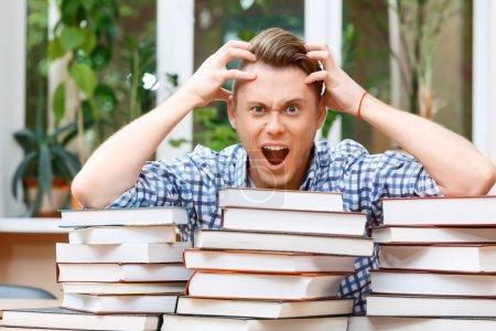 Photo pour J'ai oublié quelque chose d'important. Portrait d'un bel étudiant intelligent assis derrière une grosse pile de livres dans une bibliothèque, tenant sa tête ouvrant la bouche et regardant très choqué - image libre de droit