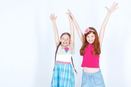 Photo for Overwhelming happiness. Pretty little girls smiling and holding their hands up while standing isolated on white background - Royalty Free Image