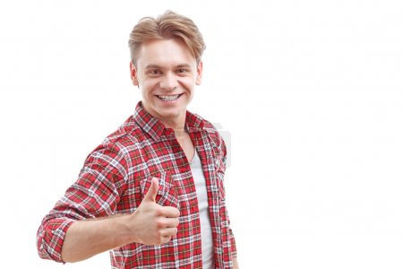 Young man thumbing up isolated on white background