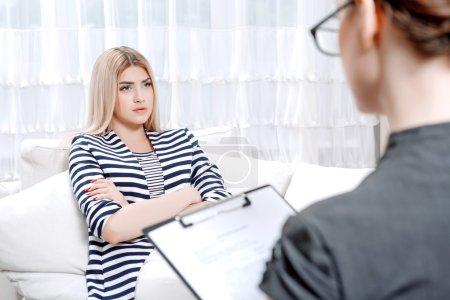 Photo pour Jeune femme blonde assise sur un canapé avec son bras croisés racontant ses problèmes, doctor avec presse-papiers à les écouter et prendre des notes au cours de la séance de thérapie, mise au point sélective - image libre de droit