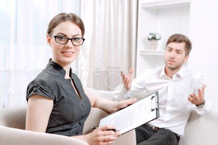 Photo pour Jeune homme portant une chemise blanche assis sur un canapé racontant ses problèmes et gesticulant, psychologue avec presse-papiers l'écoutant et nous regardant pendant la séance de thérapie, foyer sélectif - image libre de droit