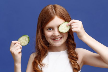 girl holding slices of cucumber