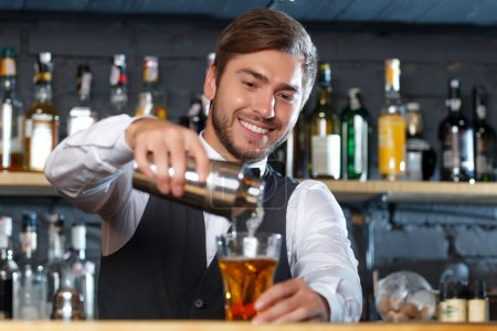 Portrait of a handsome bartender standing at the counter smiling and pouring a drink from a shaker to a glass, shelves full of bottles with alcohol on the background