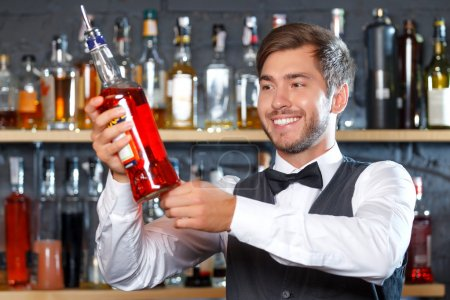 Photo for Portrait of a handsome bartender standing at the counter smiling and holding a bottle of liquor, shelves full of bottles with alcohol on the background - Royalty Free Image
