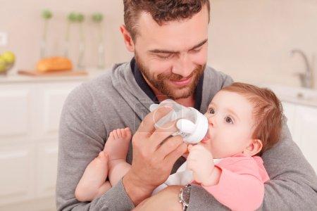Photo pour Joli moment. Agréable jeune père tenant son bébé et souriant tout en le nourrissant - image libre de droit