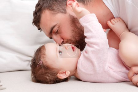 Photo for Feeling positivity. Pretty little child lying on the sofa and looking up with loving father kissing baby - Royalty Free Image
