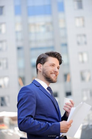 Photo for Good worker. Vivacious nice bearded businessman smiling and holding papers while drinking coffee - Royalty Free Image
