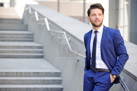 Photo for Be confident. Pleasant bearded businessman putting  his hands in pocket and leaning on the handrail with office center on background - Royalty Free Image