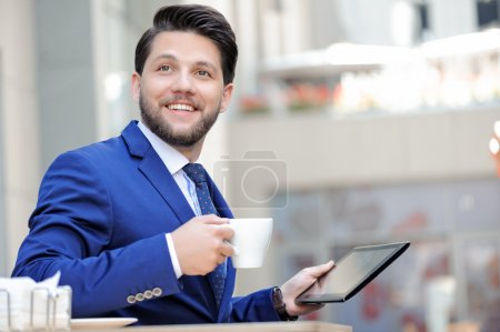 Pleasant young man sitting in cafe