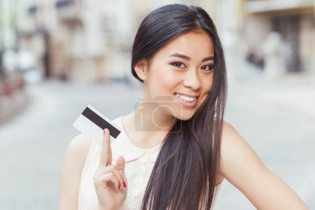 Photo for Portrait of a beautiful asian  woman with long hair, wearing beige blouse standing smiling and holding a credit card in her hand - Royalty Free Image