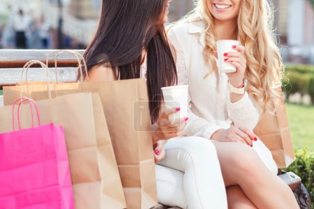 Photo for Portrait of a beautiful blond girl with long wavy hair and asian girl sitting on a bench discussing something and drinking coffee, shopping bags in front of them, selective focus - Royalty Free Image