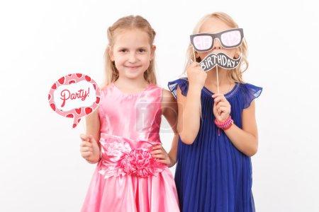 Foto de Esperando el partido. Agradables chicas alegres celebración tarjetas mientras que positividad sobre fondo blanco - Imagen libre de derechos