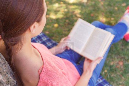 Photo pour Complot d'attrapage. Vue du dessus de la jeune femme assise sur la couverture à l'arbre dans le parc et la lecture livre intéressant - image libre de droit