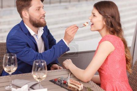 Boyfriend feeding his girlfriend in cafe