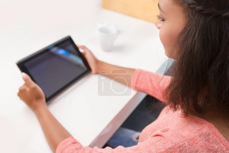 Top view of mulatto woman using tablet