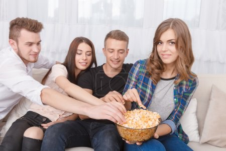 Photo for Share with me.  Pleasant contented friends eating popcorn and sitting on the sofa while feeling delighted - Royalty Free Image
