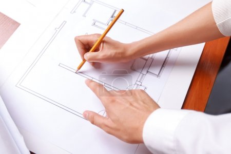 Photo for Do it in such a way. Pleasant professional architects pointing plan and drawing it while having discussion - Royalty Free Image