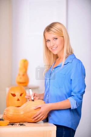 Fair haired  woman drawing on the pumpkin