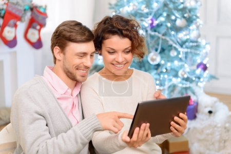 Nice couple holding laptop