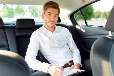 Successful businessman sitting in the car