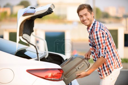 Nice man putting suitcase into the car