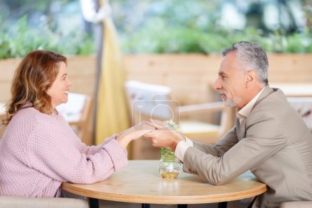 Photo pour Sensations d'excitation. Délicieux couple adulte heureux assis à la table et se tenant la main l'un de l'autre tout en faisant preuve d'amour - image libre de droit