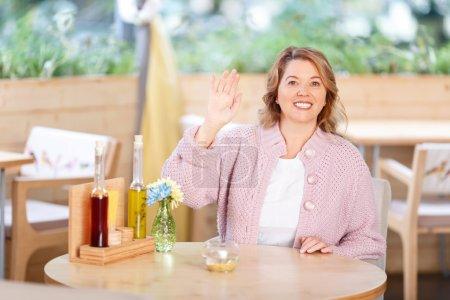 Photo pour Ravi de vous voir. Charmante femme adulte souriante et optimiste tenant la main et accueillante assise à la table du café - image libre de droit