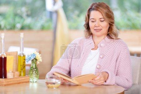 Photo pour Un roman préféré. Belle femme adulte joyeuse tenant le livre et la lecture tout en étant assis dans le café - image libre de droit