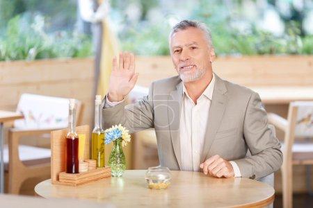Photo pour Bonsoir. Agréable gai bel homme adulte vous accueillir et lui tenir la main tout en étant assis dans le café - image libre de droit