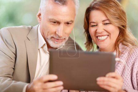 Photo pour Ravi de t'entendre. Joyeux couple adulte aimant tenant un ordinateur portable et parlant dans skype tout en faisant preuve de joie - image libre de droit