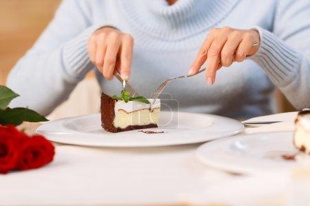 Photo pour C'est l'heure de manger. Agréable femme adulte manger du gâteau et assis à la table tout en se reposant dans le café - image libre de droit