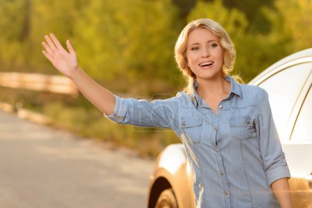 Attractive woman standing near car