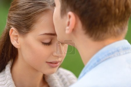 Photo pour Je ne peux pas vivre sans toi. Agréable jeune homme beau embrasser sa petite amie tout en exprimant des émotions tendres - image libre de droit