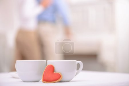 Foto de Warm your heart. Two cups of tea standing on the table with adult couple embracing on the background - Imagen libre de derechos