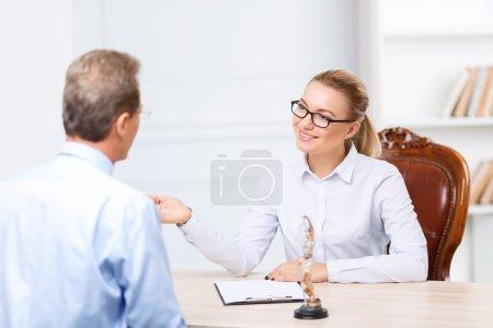 Photo pour Discutons-en. Agréable agréable enchanté avocats assis à la table et avoir une conversation tout en étant occupé au travail - image libre de droit