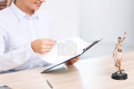 Photo pour Occupé au travail. Avocat professionnel de femme retenant le dossier et s'asseyant à la table tout en faisant son travail - image libre de droit