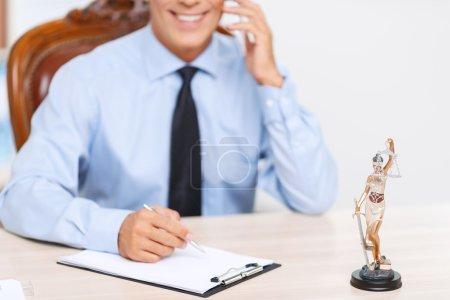 Photo pour Avocat occupé. Gros plan de professionnel souriant ravi avocat écrivant et parlant sur téléphone mobile tout en ayant la conversation - image libre de droit