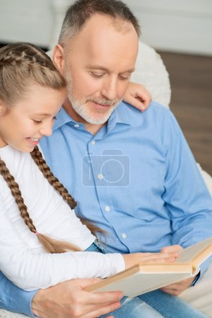 Photo pour Impliqué dans un conte de fées. Grand-père agréable et petite fille assise dans le fauteuil et le livre de lecture tout en se sentant ravie - image libre de droit