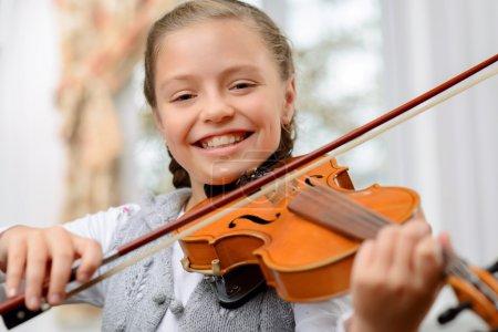 Photo pour Plein de joie. Contenu gai petite fille tenant violon arc et violon tout en apprenant à jouer - image libre de droit