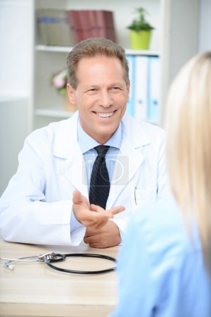 Smiling cardiologist talking to the patient