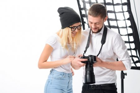 Model and photographer are looking through the shots.