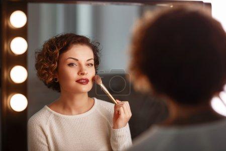 Photo pour J'adore ça. Gros plan de attrayant jeune femme agréable tenant brosse et maquillage tout en étant assis devant le miroir - image libre de droit