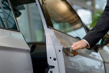 Photo pour Jetez un coup d'œil à l' Fermez-vous vers le haut de la main d'homme atteignant et ouvrant une porte de voiture - image libre de droit
