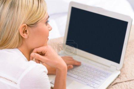 Photo pour Gadget nécessaire. Jeune voyageur femelle attrayante couché dans son lit et travaillant sur son ordinateur portable - image libre de droit