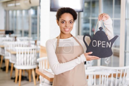Smiling waitress holding an opening sign.