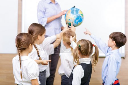 Group of children and teacher holding a globe.