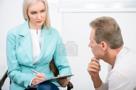 Senior man speaking with psychologist